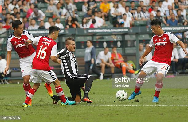 Roberto Pereyra of Juventus FC fight for the ball with Chan Siu Kwan Philip of South China during the match between Juventus FC and South China of...