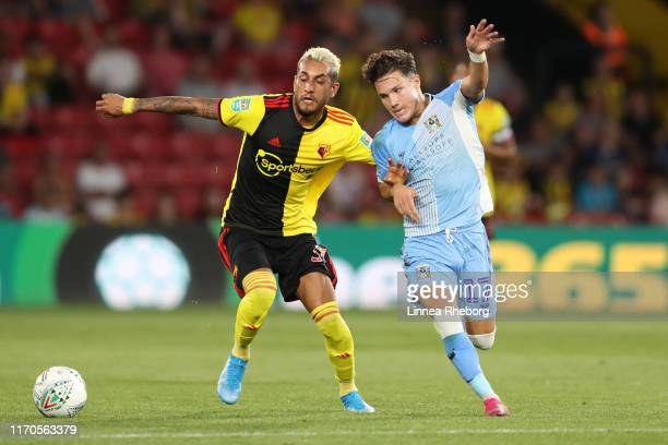 Roberto Pereyra of Watford and Callum O'Hare of Coventry City battle for the ball during the Carabao Cup Second Round match between Watford and...