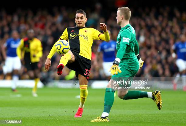Roberto Pereyra of Watford FC and Jordan Pickford of Everton in action during the Premier League match between Watford FC and Everton FC at Vicarage...