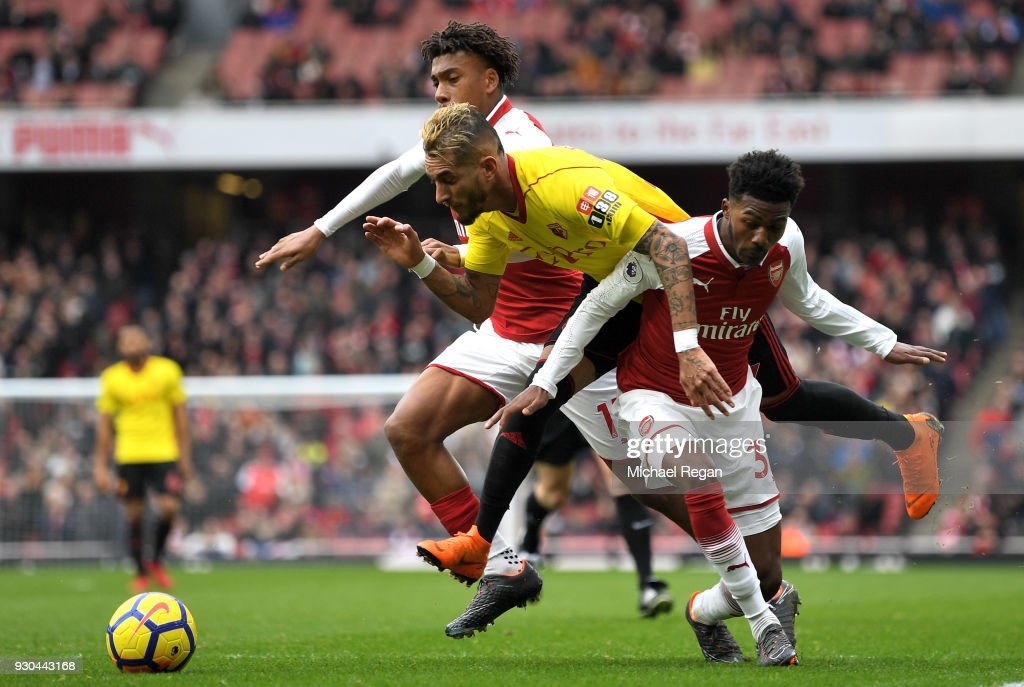 Roberto Pereyra of Watford is fouled by Ainsley Maitland-Niles of Arsenal and Alex Iwobi of Arsenal for a penalty during the Premier League match between Arsenal and Watford at Emirates Stadium on March 11, 2018 in London, England.