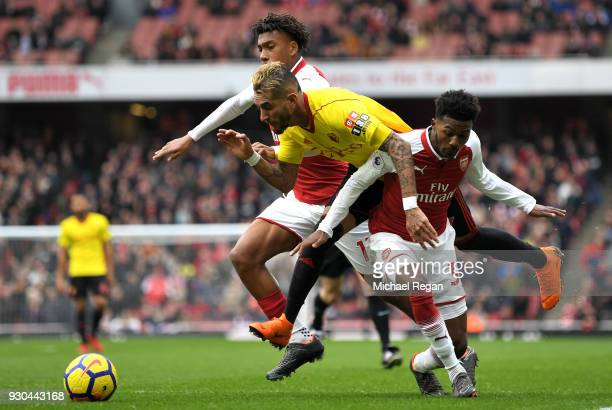 Roberto Pereyra of Watford is fouled by Ainsley Maitland-Niles of Arsenal and Alex Iwobi of Arsenal for a penalty during the Premier League match...