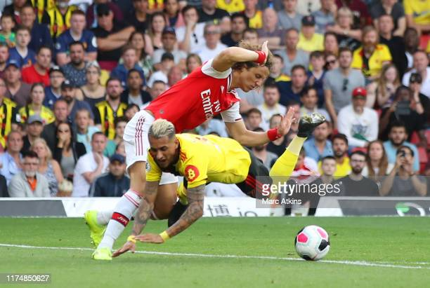 Roberto Pereyra of Watford is fouled by David Luiz of Arsenal for a penalty during the Premier League match between Watford FC and Arsenal FC at...