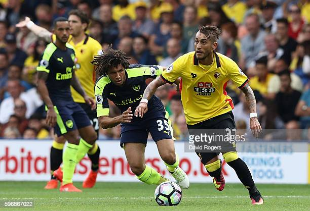 Roberto Pereyra of Watford runs with the ball watched by Mohamed Elneny during the Premier League match between Watford and Arsenal at Vicarage Road...