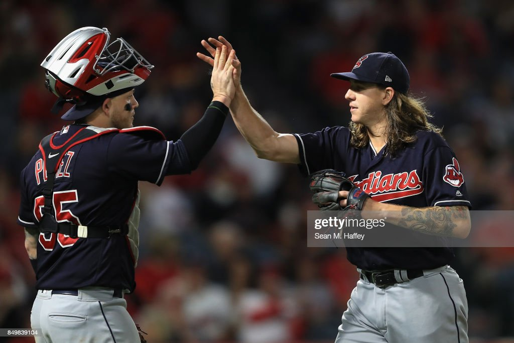 Roberto Perez #55 congratulates Mike Clevinger #52 of the Cleveland Indians after ending the sixth inning on a ground out by Mike Trout #27 of the Los Angeles Angels of Anaheim in a game at Angel Stadium of Anaheim on September 19, 2017 in Anaheim, California.