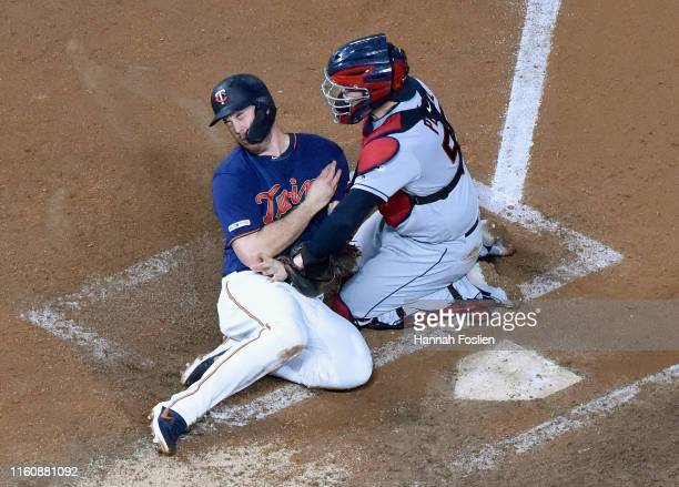 Roberto Perez of the Cleveland Indians defends home plate against C.J. Cron of the Minnesota Twins during the fourth inning of the game on August 10,...