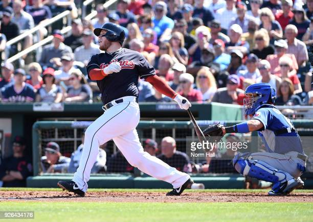 Roberto Perez of the Cleveland Indians follows through on an RBI double during the second inning as Robinson Chirinos of the Texas Rangers looks on...