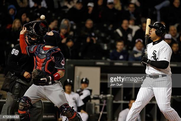Roberto Perez of the Cleveland Indians takes off his mask after losing control of the ball as Jose Abreu of the Chicago White Sox watches during the...