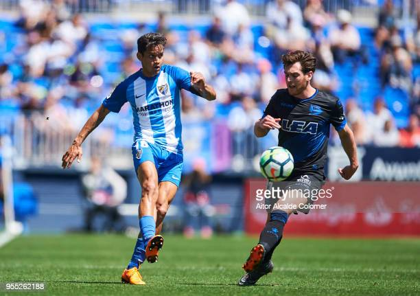 Roberto Rosales of Malaga competes for the ball with Ibai Gomez of Deportivo Alaves during the La Liga match between Malaga and Deportivo Alaves at...