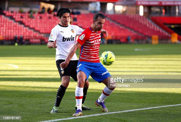 Roberto Soldado of Granada CF battles for possession with Carlos Soler of Valencia CF during the La Liga Santander match between Granada CF and...