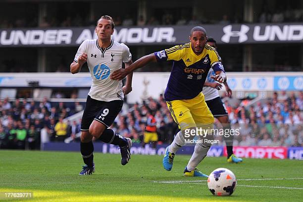 Roberto Soldado of Spurs and Ashley Williams of Swansea chase down the ball during the Barclays Premier League match between Tottenham Hotspur and...