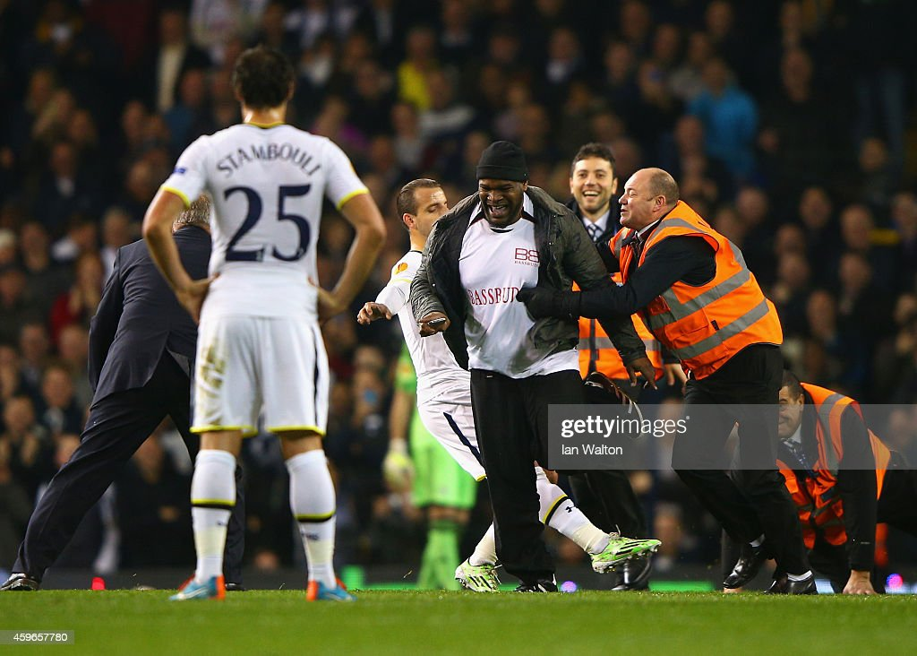 Roberto Soldado of Spurs attempts to tackle a pitch invader as stewards apprehend him during the UEFA Europa League group C match between Tottenham Hotspur FC and FK Partizan at White Hart Lane on November 27, 2014 in London, United Kingdom.
