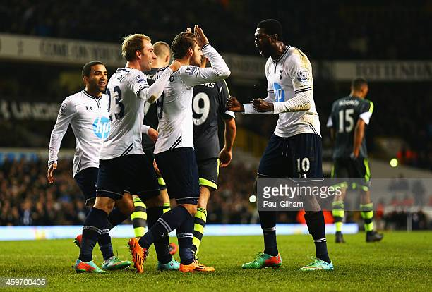 Roberto Soldado of Tottenham Hotspur is congratulated by team mates including Emmanuel Adebayor and Christian Eriksen after scoring from the penalty...
