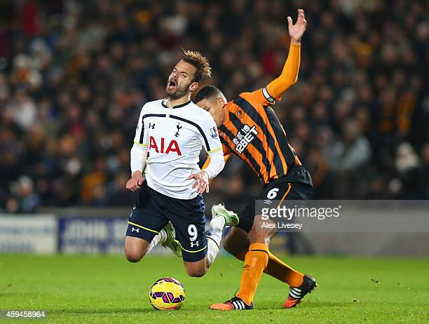 Roberto Soldado of Tottenham Hotspur is tackled by Curtis Davies of Hull City during the Barclays Premier League match between Hull City and...
