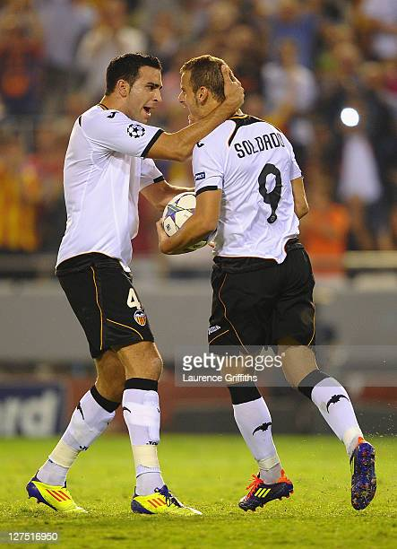 Roberto Soldado of Valencia celebrates scoring from the penalty spot with team mate Adil Rami during the UEFA Champions League Group E match between...