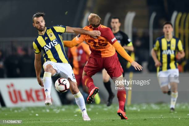 Roberto Soldado Rillo of Fenerbahce and Semih Kaya of Galatasaray compete for the ball during the Turkish Super Lig match between Fenerbahce and...