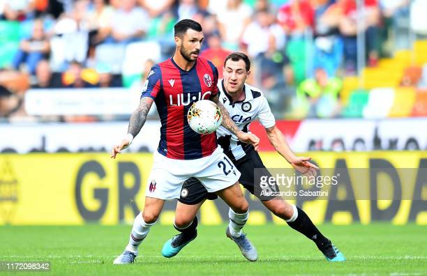 Roberto Soriano of Bologna FC competes for the ball wit competes for the ball with Mato Jajalo of Udinese Calcio during the Serie A match between...