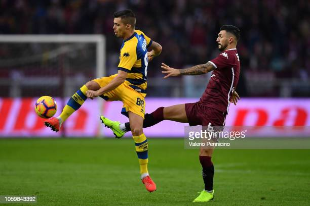 Roberto Soriano of Torino FC competes with Alberto Grassi of Parma Calcio during the Serie A match between Torino FC and Parma Calcio at Stadio...