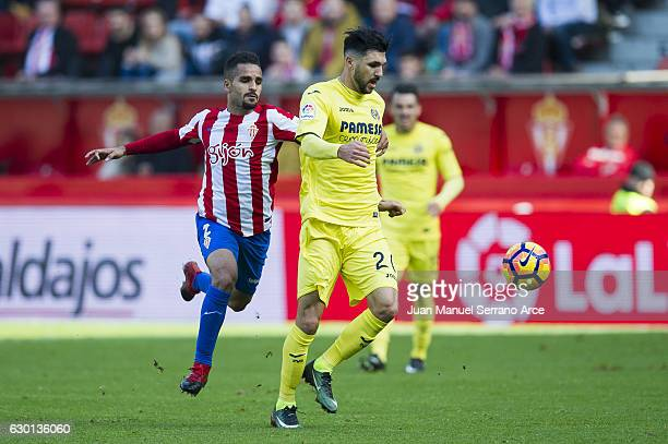 Roberto Soriano of Villarreal CF duels for the ball with Douglas Pereira of Real Sporting de Gijon during the La Liga match between Real Sporting de...