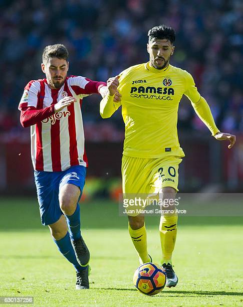 Roberto Soriano of Villarreal CF duels for the ball with Moises Gomez of Real Sporting de Gijon during the La Liga match between Real Sporting de...