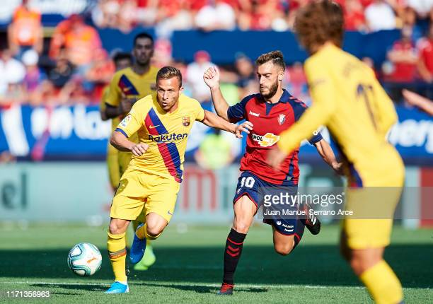 Roberto Torres of CA Osasuna competes for the ball with Arthur Melo of FC Barcelona during the Liga match between CA Osasuna and FC Barcelona at...
