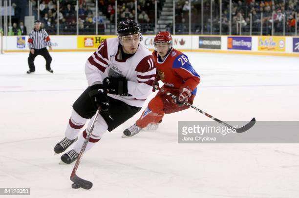 Roberts Bukarts of Latvia carries the puck as Evgeni Dadonov of Russia chases him at the Civic Centre on December 26, 2008 in Ottawa, Ontario, Canada.