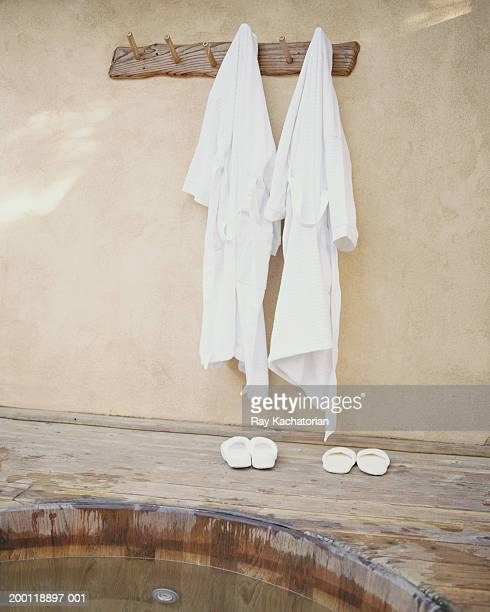 robes hanging on wall by hot tub - his and hers stock pictures, royalty-free photos & images