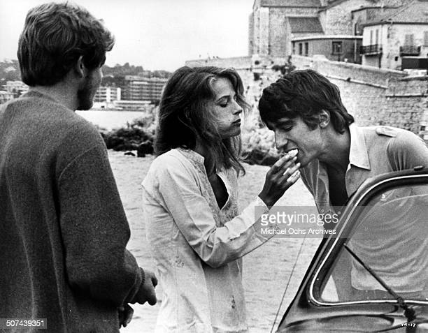"Robie Porter looks on as Charlotte Rampling feeds Sam Waterston in a scene from the movie ""Three"" , circa 1967."