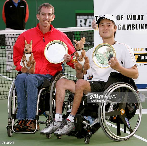 Robin Ammerlaan of the Netherlands and Shingo Kunieda of Japan pose with the trophies after winning the doubles wheelchair final match on day...