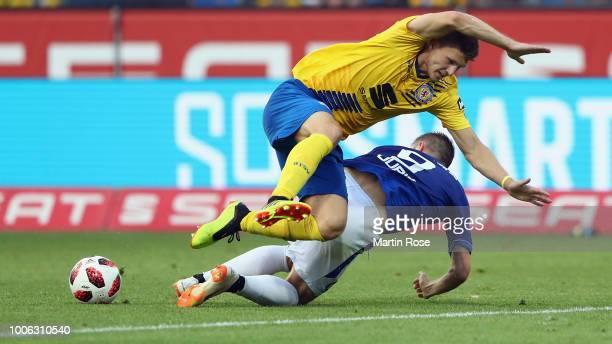 Robin Becker of Braunschweig falls over Marvin Pourie of Karlsruhe during the 3 Liga match between Eintracht Braunschweig and Karlsruher SC at...