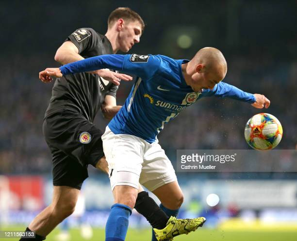 Robin Becker of Eintracht Braunschweig and Korbinian Vollmann of Hansa Rostock battle for the ball during the 3 Liga match between Hansa Rostock and...
