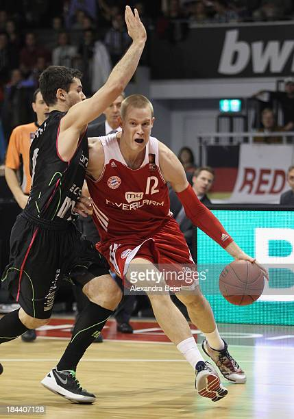 Robin Benzing of Bayern Muenchen is tackled by Nicolai Simon of medi Bayreuth during the Basketball Bundesliga match between FC Bayern Muenchen and...