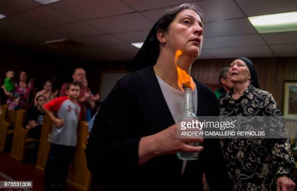 Robin Brandon holds fire to her neck as she spins during a Pentecostal serpent handlers service at the House of the Lord Jesus church in Squire West...