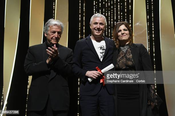 Robin Campillo poses on the stage with jury member Agnes Jaoui and director CostaGavras after receiving the Grand Prix for the movie '120 Beats Per...