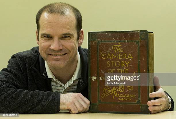 Robin Coombs poses with a Photo album of J Taylor Maclagan a photographer from the earlier part of the 20th century who earned his wages taking...