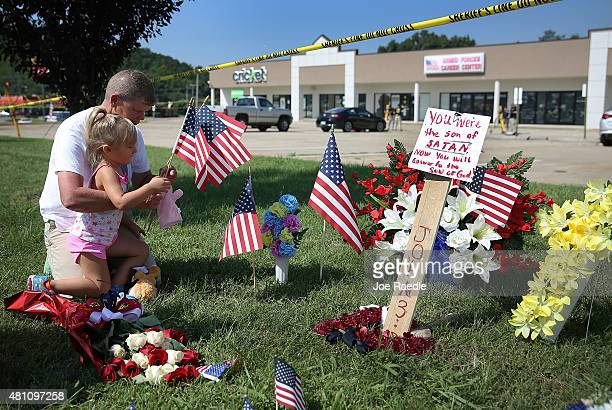 Robin Duckett and Brooklynn Crawford pay their respects to those killed while visiting a memorial placed in front of the Armed Forces Career...