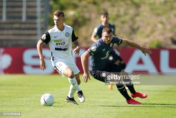 Robin Fellhauer of SV Elversberg is challenged by Max Dittgen of St Pauli during the DFB Cup first round match between SV Elversberg and FC St. Pauli...