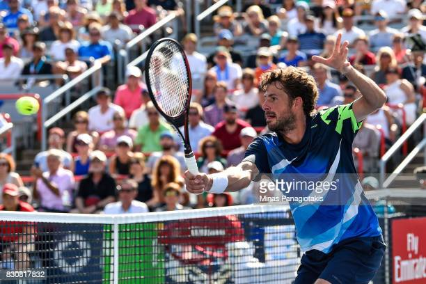 Robin Haase of Netherlands hits a return near the net against Roger Federer of Switzerland during day nine of the Rogers Cup presented by National...