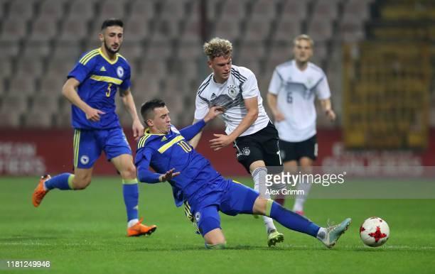Robin Hack of Germany is tackled by Marijan Cavar of Bosnia and Herzegovina during the UEFA U21 Championship Qualifying match between Bosnia and...