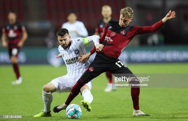 Robin Hack of Nuernberg is challenged by Jerome Gondorf of Karlsruhe during the Second Bundesliga match between 1. FC Nürnberg and Karlsruher SC at...