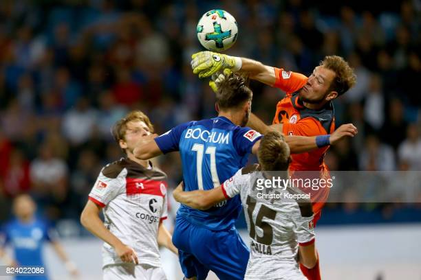 Robin Himmelmann of St Pauli saves the ball against Dimitrios Diamantakos of Bochum during the Second Bundesliga match between VfL Bochum 1848 and FC...