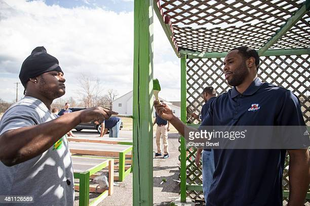 Robin Hopkins shows Scoop Jardine of the Tulsa 66ers how to paint a pergola during the NBA DLeague community relations event at A New Leaf a...