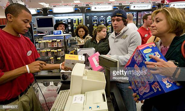 Robin Horne right with her son Colby second from right purchases a Kodak digital camera along with other items from Target cashier Aaron Clark left...