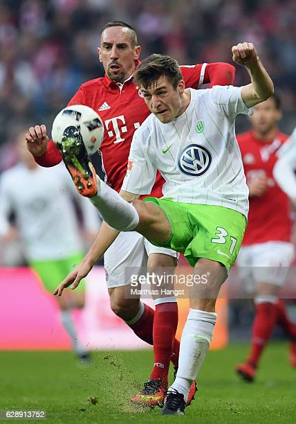 Robin Knoche of Wolfsburg clears the ball ahead of Franck Ribery of Muenchen during the Bundesliga match between Bayern Muenchen and VfL Wolfsburg at...