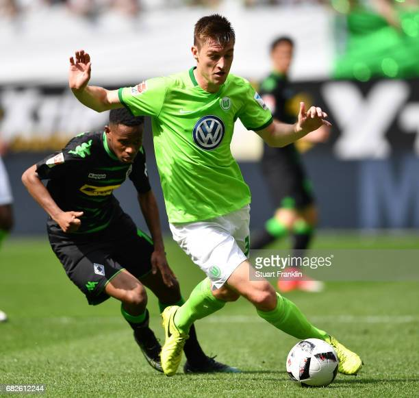 Robin Knoche of Wolfsburg is challenged by Ibrahima Traore of Gladbach during the Bundesliga match between VfL Wolfsburg and Borussia...