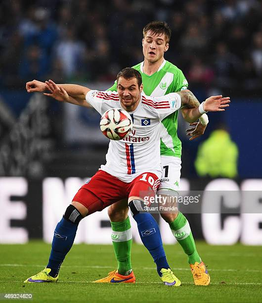 Robin Knoche of Wolfsburg is challenged by Pierre Michel Lasogga of Hamburg during the Bundesliga match between Hamburger SV and VfL Wolfsburg at...