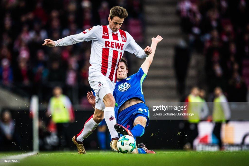 Robin Knoche (R) of Wolfsburg tackles Lukas Kluenter (L) of Koeln during the Bundesliga match between 1. FC Koeln and VfL Wolfsburg at RheinEnergieStadion on December 16, 2017 in Cologne, Germany.