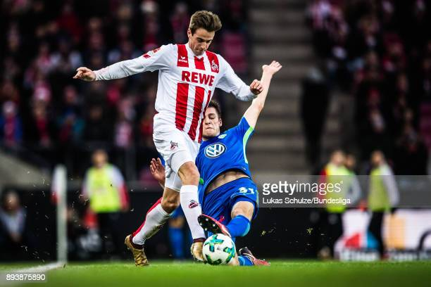 Robin Knoche of Wolfsburg tackles Lukas Kluenter of Koeln during the Bundesliga match between 1 FC Koeln and VfL Wolfsburg at RheinEnergieStadion on...