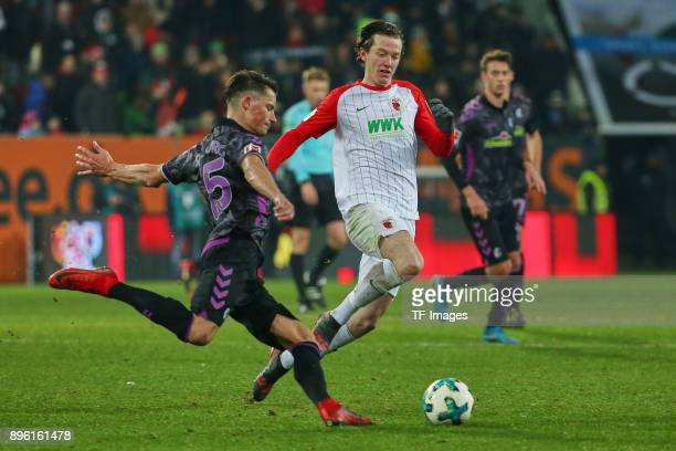 Robin Koch of Freiburg and Michael Grogoritsch of Augsburg battle for the ball during the Bundesliga match between FC Augsburg and SportClub Freiburg...