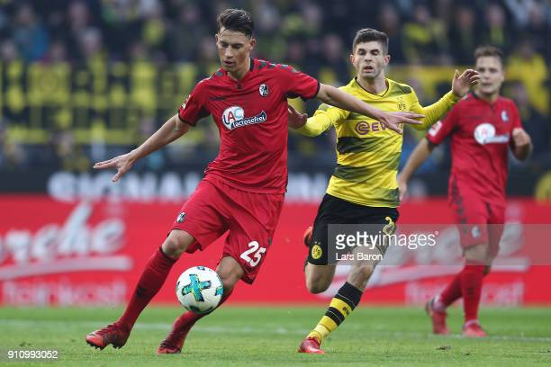 Robin Koch of Freiburg runs with the ball past Christian Pulisic of Dortmund during the Bundesliga match between Borussia Dortmund and Sport-Club...