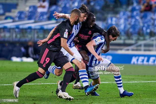 Robin Le Normand and Aritz Elustondo of Real Sociedad battle for the ball with Ferland Mendy and Karim Benzema of Real Madrid during the La Liga...